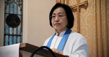 An Asian-American woman wearing glasses and a white pastor's robe stands in front of a pulpit.