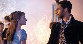 A woman in a man stare at each other in front of a background filled with sparkles.