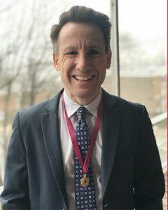 Man in suit wearing medal around neck