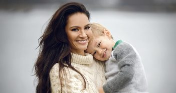 A smiling woman holding a toddler in her arms