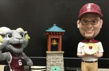 Bobbleheads of a man, a Ram, and a miniature of the victory bell