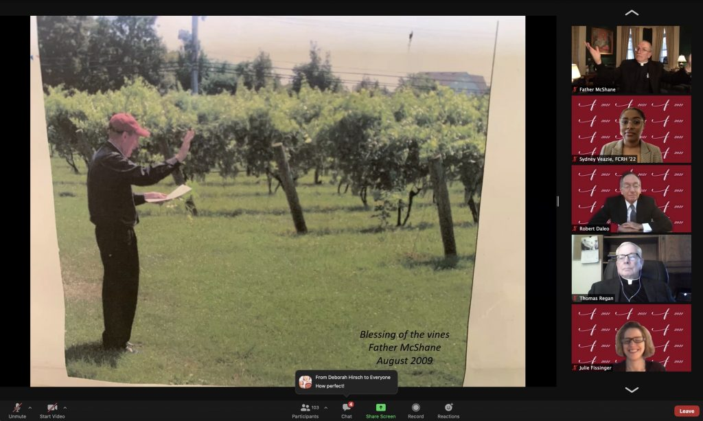 A man standing in front of a vineyard with a book