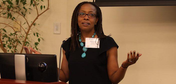 Marjorie Parker, FCRH '90, stands a podium.