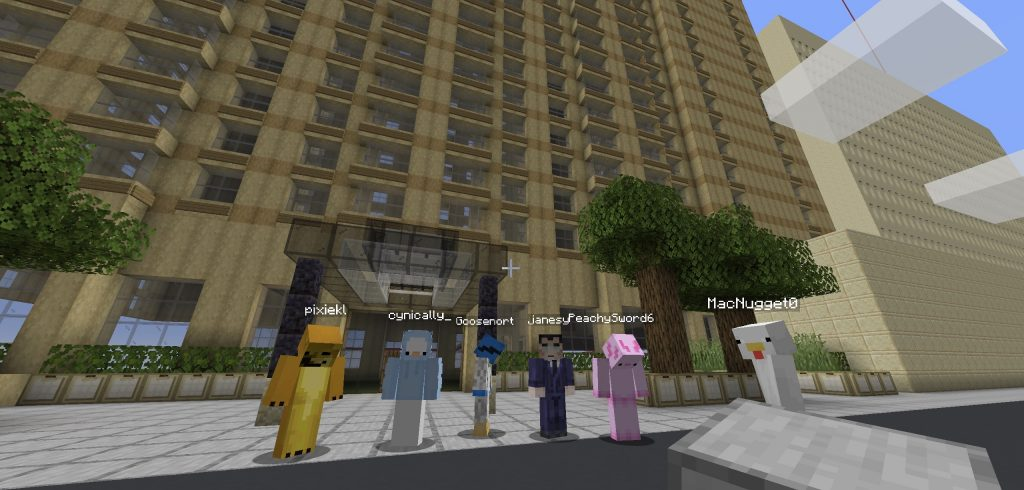 Five video game avatars with a blocky texture stand in front of a digital building.