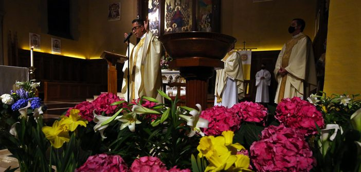 Priest on altar in University Church with flowers