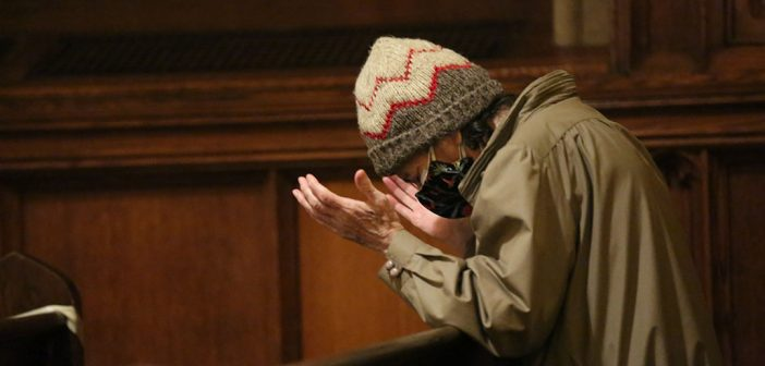 Man in knit hat praying in University Church