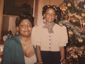 A woman and a girl smile in front of a Christmas tree.