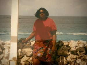 A woman wearing sunglasses, a red shirt, and a floral skirt stands in front of the ocean.