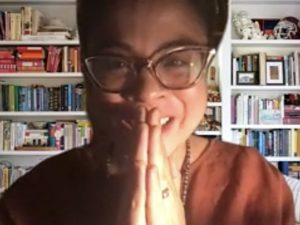 A woman wearing glasses clasps her hands in front of a background filled with books.