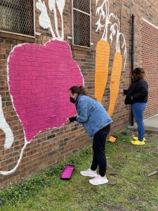 A woman wearing a jean jacket and black pants paints a purple beet on a brick wall.