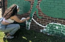A girl wearing overalls and a mask squats in front of a brick mural and paints with a green brush.