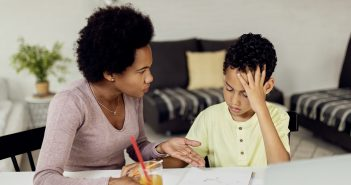 A woman with an afro and light pink shirt speaks to a boy with curly hair and a yellow T-shirt at a white desk.