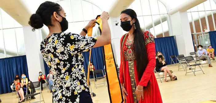 Student receiving yellow stole at AAPI graduation celebration in red dress