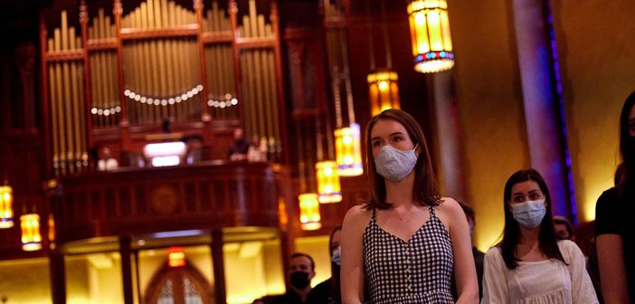 a woman with a mask stands in church