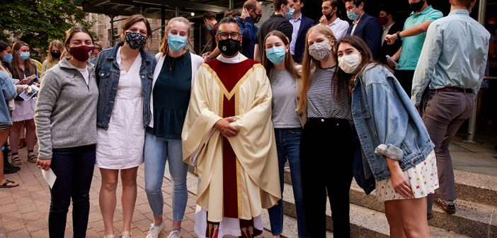 A group of students stand together with a priest outsid of the University Church