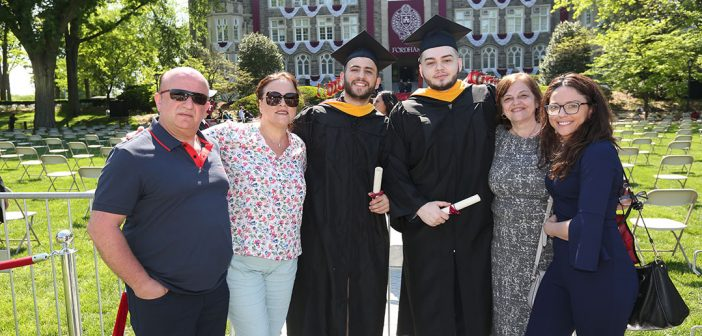Two men grads and their families