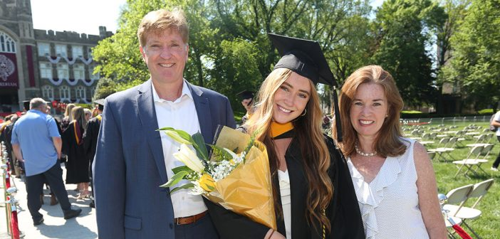 A grad and her family with flowers