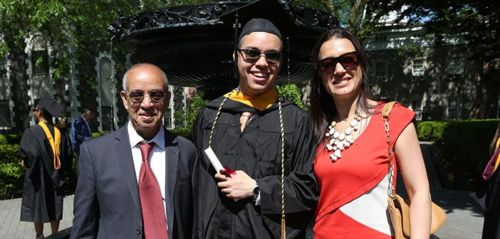 A grad with sunglasses and his parents/family