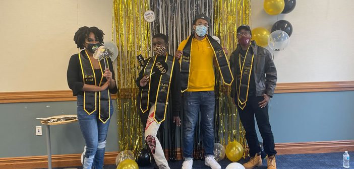 Students posing with balloons at Black graduation celebration