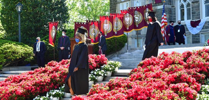 Grads processing past flowers and banners