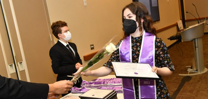 Student receiving white rose at LGBTQ Lavender Graduation
