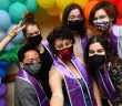 Students posing in front of rainbow balloons at LGBTQ Lavender Graduation with lavender stoles
