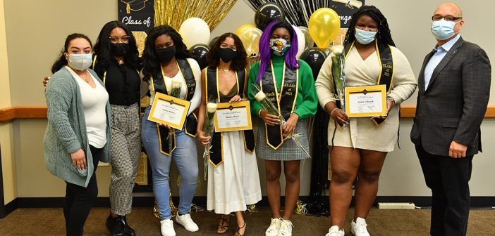 Students posing with diplomas in front of ballons at Black graduation celebration