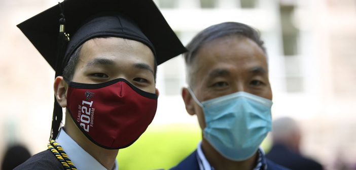 Graduate and his father in masks