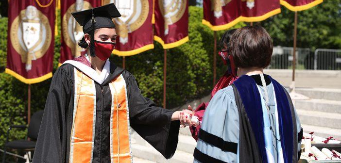 receiving a diploma from Dean Laura Auricchio