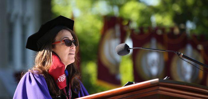 Dean Donna Rapaccioli in purple robes at podium