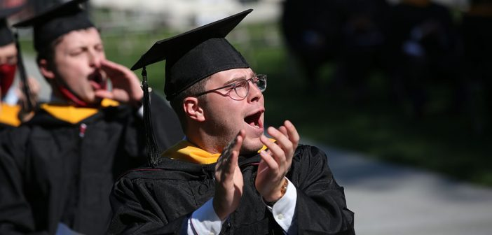 Man grad clapping in seat