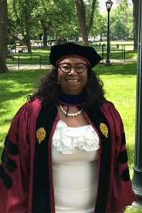 Magalie Exavier-Alexis, a 2021 GSE graduate, posing with trees in the background.