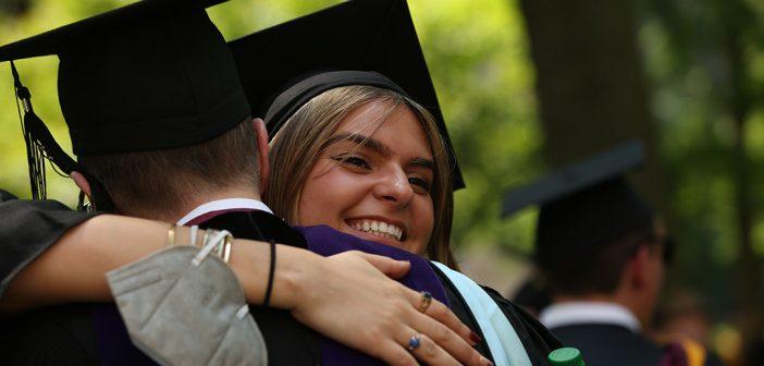 two grads hugging
