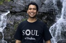 "A man wearing a black t-shirt that says ""Soul of Fordham"" smiles in front of a waterfall."