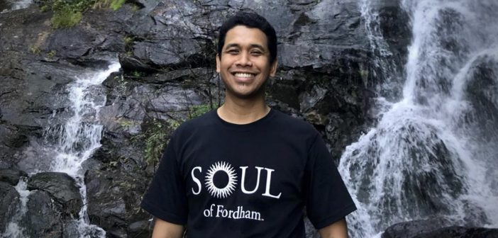 """A man wearing a black t-shirt that says """"Soul of Fordham"""" smiles in front of a waterfall."""