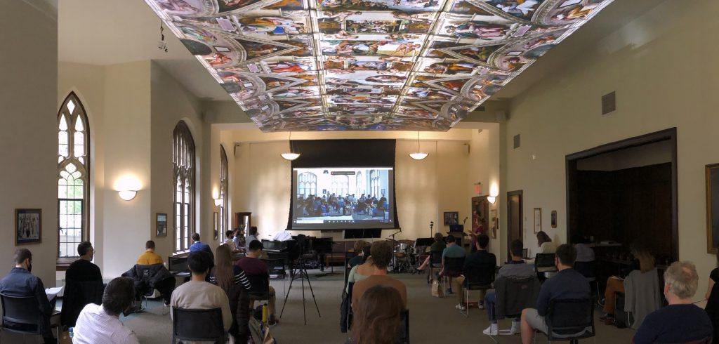People sit in chairs spaced six feet apart in a large room with a painting on the ceiling.