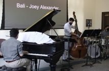 Three men each play an instrument: a piano, a cello, and a drum set, in a room with white walls.