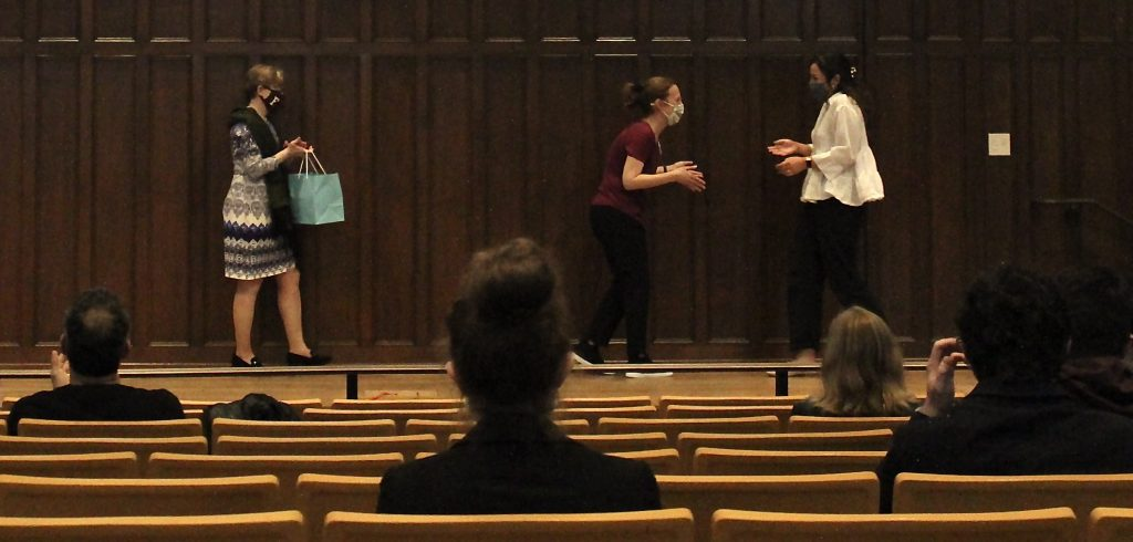 A woman rushes toward another woman for a hug in an auditorium.