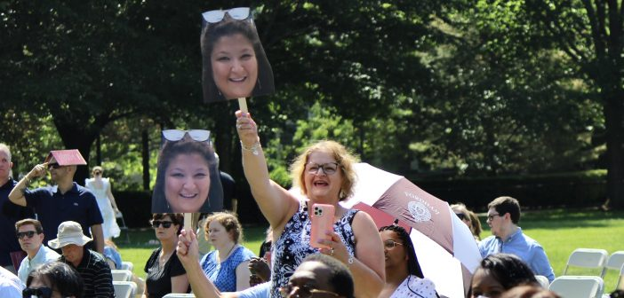 A family member holding a cardboard cutout of a graduate's face.