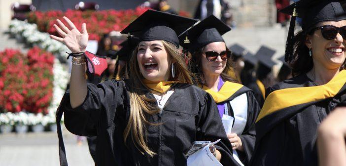 A graduaten smiling and waving.
