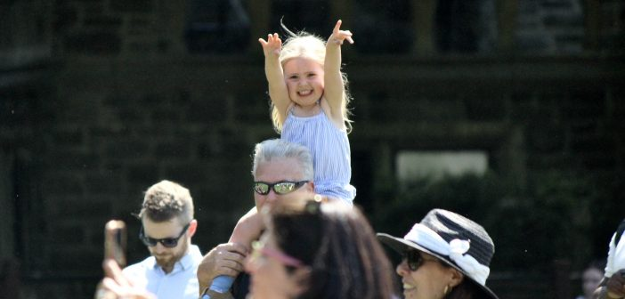 A child on someone's shoulders in the crowd.