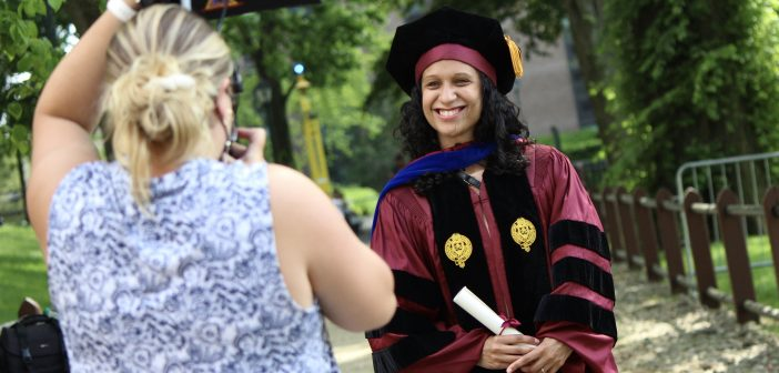A graduate posing for a photo.