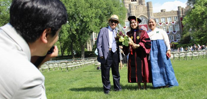 A GSE graduate posing for a photo with two family members.