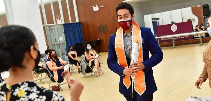 Male graduate with orange stole at Latinx graduation