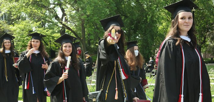 grad in line pointing at camera with diploma