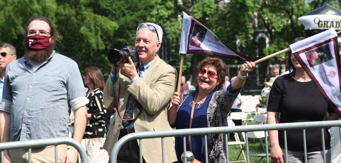 parents waving banners and taking photos