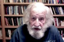 A man with white head and beard hair talks in front of a bookshelf