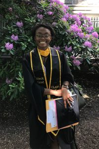 Darlyn Smith, a 2021 GSE graduate, posing in front of flowers.