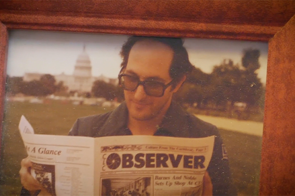 A framed photo of Mitch Berger, FCLC '83, holding a copy of The Observer, the newspaper of which he was one of the founding editors.