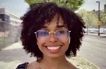 A woman with black curly hair and glasses smiles in front of a street.